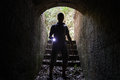 Young Man With A Flashlight Enters Stone Tunnel Stock Photos - 58968033