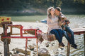 Young Future Parents And Their Dog In A Funny Costume Sitting On A Wooden Bridge And Having Picnic Near Lake Royalty Free Stock Photography - 59017597