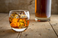 Whisky Glass And Bottle Golden Brown Ice On Wooden Surface In Saloon Bar Pub Stock Photos - 59249973