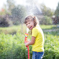 Cheerful Kid Watering Plants From Hose Spray In Stock Photos - 59478643