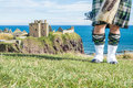 Traditional Scottish Bagpiper In Full Dress Code At Dunnottar Castle Stock Image - 59590791