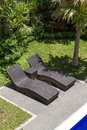 Couple Of Sun Loungers Beside The Pool In Tropical Garden.  Bali, Indonesia Royalty Free Stock Photography - 59592197