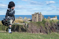 Traditional Scottish Bagpiper In Full Dress Code At Dunnottar Castle Stock Photo - 59604720