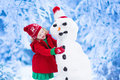 Little Girl Building A Snow Man In Winter Stock Photography - 59615972