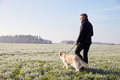 Mature Man Walking Dog In Frosty Landscape Stock Images - 59714064