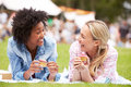 Two Female Friends Enjoying Cupcakes At Outdoor Summer Event Royalty Free Stock Photo - 59726565