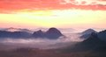 Red Misty  Landscape Panorama In Mountains. Fantastic Dreamy Sunrise On Rocky Mountains.  Foggy Misty Valley Below Royalty Free Stock Image - 59790706