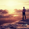 Alone Hiker In White Shirt And Red Cap Stand On Peak Of Rock In Rock Empires Park And Watch Over Misty And Foggy Valley To Sun. Th Stock Photo - 59845830