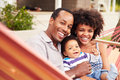 Happy Couple�with Young Child Sitting In A Hammock Royalty Free Stock Image - 59872206