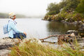 Senior Woman With A Hat Sitting By The Lake, Admiring The View Royalty Free Stock Image - 59873996