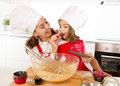 Happy Mother Baking With Little Daughter Eating Chocolate Bar Used As Ingredient While Teaching The Kid Royalty Free Stock Photo - 59905565