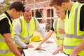 Builder On Building Site Discussing Work With Apprentice Stock Photos - 59931793