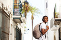 Smiling African Travel Man With Bag Listening To Music Stock Photo - 59944510