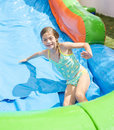 Smiling Little Girl Playing On An Inflatable Slide Bounce House Royalty Free Stock Image - 59997596