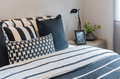 Black And White Pillows And Blanket On Bed With Black Lamp On Ta Royalty Free Stock Image - 60209416