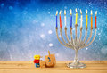 Low Key Image Of Jewish Holiday Hanukkah With Menorah (traditional Candelabra) And Wooden Dreidels (spinning Top) Royalty Free Stock Photography - 60253777