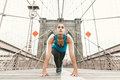 Beautiful Girl Making Stretching At Early Morning Before Running. Brooklyn Bridge And New York Skyline In The Background Stock Images - 60297324