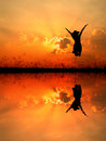 Jumping Woman And Sunset Silhouette,water Reflect Royalty Free Stock Images - 60316759
