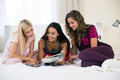 Three Girlfriends Reading Magazine On The Bed Stock Photography - 60422322