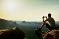 Tourist In Grey T-shirt Takes Photos With Smart Phone On Peak Of Rock. Dreamy Hilly Landscape Below, Orange Pink Misty Sunrise In Stock Photos - 60506473