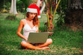Young Lady Is Sitting On The Grass With A Laptop In A Christmas Hat Stock Photos - 60516853