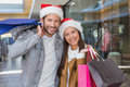 Young Happy Couple Holding Shopping Bags With Christmas Hats On Their Hats Stock Photo - 60534020