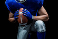 Mid Section Of American Football Player Kneeling While Holding Ball Stock Photo - 60541850