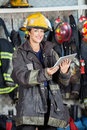 Happy Firewoman Holding Digital Tablet At Fire Stock Photography - 60552142