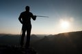 Tourist Guide Show The Right Way With Pole In Hand. Hiker With Sporty Backpack Stand On Rocky View Point Above Misty Valley. Sunny Royalty Free Stock Photos - 60564598