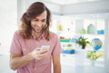 Hipster Smiling While Looking At Mobile Phone Stock Image - 60566111