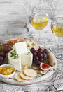 Delicious Appetizer To Wine - Ham, Cheese, Grapes, Crackers, Figs, Nuts, Jam, Served On A Light Wooden Board, And Two Glasses With Royalty Free Stock Photography - 60679937