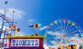 Ticket Booth And Rides At A Carnival Against Blue Sky Stock Images - 60718404