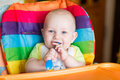 Adorable Baby Eating In High Chair Royalty Free Stock Images - 60718409