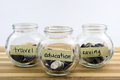Coins In Glass Container With Travel, Saving And Education Labels Royalty Free Stock Photo - 60808225