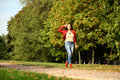 Young Woman In Fashion Red Jacket And Blue Jeans Walking In Autu Stock Images - 60815704