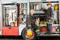 Confident Firefighters Standing On Truck At Fire Royalty Free Stock Photos - 60815808