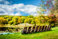 A Row Of Empty Chairs Under Dramatic Crisp Autumn Sky Over Tyrrel Lake At Innisfree Garden, Millbrook, New York Stock Photo - 60827830
