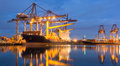 Containers Loading By Crane At Dark Sunset Royalty Free Stock Images - 60935459