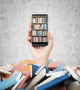 A Hand Holds A Smartphone With A Book Shelf On The Screen. A Heap Of Colourful Books. A Concept Of Education And Technology. Stock Photography - 60972172