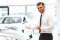 Salesman Standing At The Car Showroom And Showing New Cars Stock Photo - 61013390