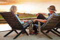 Senior Couple Relaxing Near The Lake Royalty Free Stock Images - 61059189