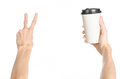Breakfast And Coffee Theme: Man S Hand Holding White Empty Paper Coffee Cup With A Brown Plastic Cap Isolated On A White Backgroun Stock Image - 61109651