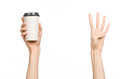 Breakfast And Coffee Theme: Man S Hand Holding White Empty Paper Coffee Cup With A Brown Plastic Cap Isolated On A White Backgroun Royalty Free Stock Photo - 61109765