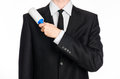 Dry Cleaning And Business Theme: A Man In A Black Suit Holding A Blue Sticky Brush For Cleaning Clothes And Furniture From Dust Is Royalty Free Stock Image - 61112856
