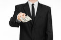 Money And Business Theme: A Man In A Black Suit Holding A Bill Of 100 Dollars And Features A Hand Gesture On An Isolated White Bac Royalty Free Stock Images - 61116059