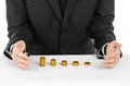 Money And Business Theme: A Man In A Black Suit Indicates The Chart Bars Of Gold Coins On A White Table In The Studio On A White B Royalty Free Stock Images - 61116789