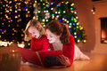 Mother And Daughter Reading At Fire Place On Christmas Eve Royalty Free Stock Images - 61195699