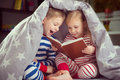Happy Siblings Reading Book Under Cover Royalty Free Stock Photography - 61420017