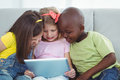 Happy Kids Sitting Together With A Tablet Stock Photo - 61438100