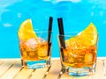Two Glasses Of Spritz Aperitif Aperol Cocktail With Orange Slices And Ice Cubes On Swimming Pool Background Stock Photos - 61491883